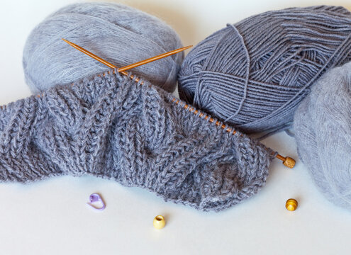 Start knitting a warm gray wool and mohair scarf in bulk knit. Skeins of yarn on a white background. Winter handicrafts and hobby. Close-up view