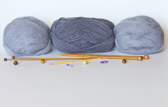 Materials for hand knitting: three gray woolen balls of yarn and a set of wooden knitting needles on a white background. Free space for text. Needlework concept. Mock up, copy space, close-up
