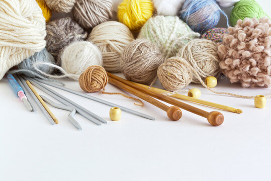 A set of accessories for hand knitting: metal, plastic and wooden knitting needles, crochet hooks, balls of woolen and boucle yarn on white background. Empty space for text. Still life, copy space