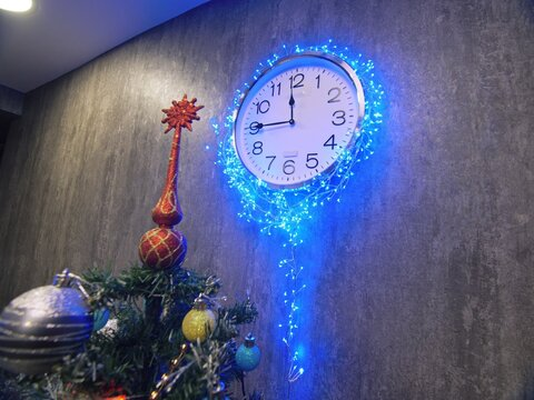 Clock and christmas tree, balls, toys. Timelapse New Year. The clock is hanging on the wall. Time on the clock is 23.45 to 00.00.