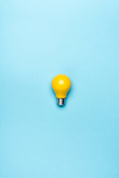 top view yellow light bulb on blue