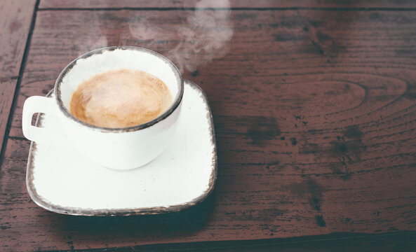 close-up view of cup of steaming hot italian espresso on red rustic wooden table