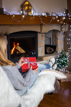 Woman holding christmas present in hands near fireplace in cozy home interior. Woman sitting at chair and opening christmas gift box
