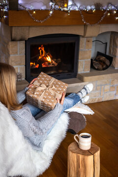 Woman holding christmas gift box and sitting on chair near fireplace. Coffee cup on tree stump in cozy home interior. Enjoyment of christmas holiday