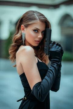 A beautiful girl in an elegant black dress. Young woman holding a gun.