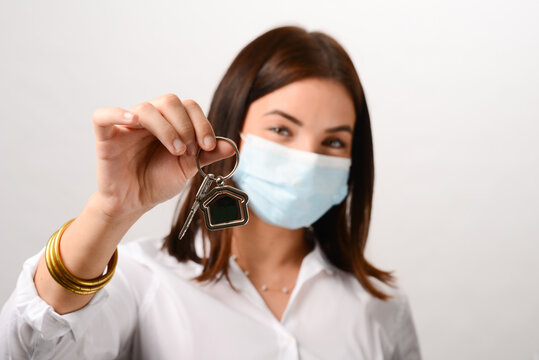 portrait of beautiful young real estate agent business woman wearing surgical mask and holding house keys