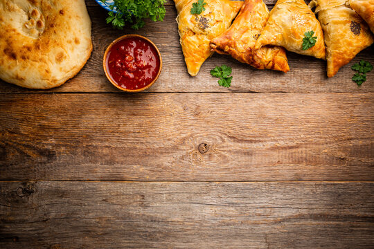 Samsa or samosas with meat or vegetables and pita with tomato sauce on wooden background. Traditional asian food. Top view.