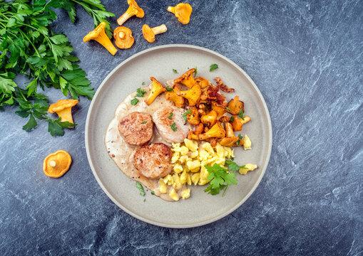 Modern Style traditionelle gebratene Filet Medaillons vom Schwein in Rahmsauce mit Pfifferlinge und Spaetzle serviert als Draufsicht auf einem Nordic Design Teller mit Textfreiraum