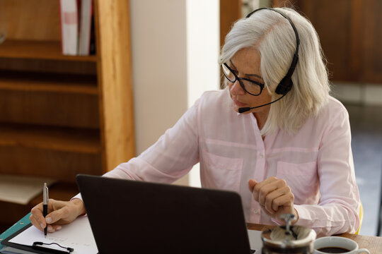 Senior caucasian woman using a laptop and wearing headphones