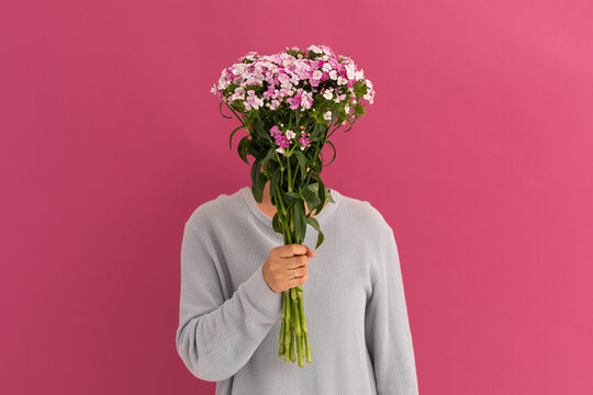 Caucasian woman covering her face with bouquet of flowers on pink
