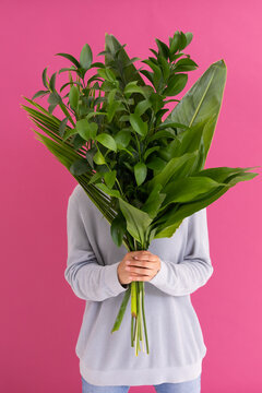 Caucasian woman covering her face with bunch of leaves on pink