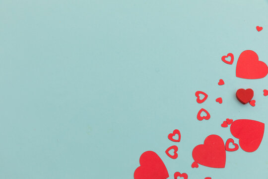 High angle view of red hearts scattered on blue background