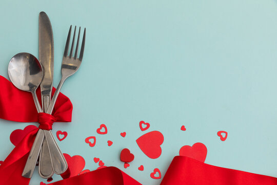 High angle view of cutlery with red ribbon and metallic hearts on blue background