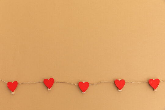 String with five red hearts on brown background