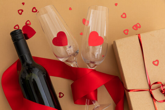 Bottle of wine, glasses with red hearts and present on brown background