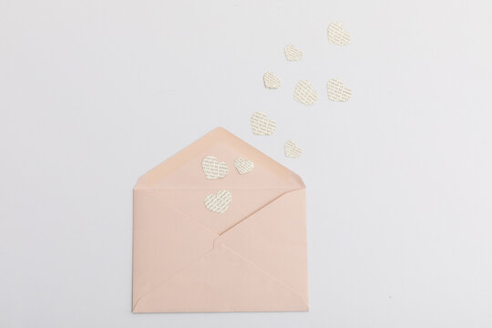 Pink envelope and multiple hearts with text on white background