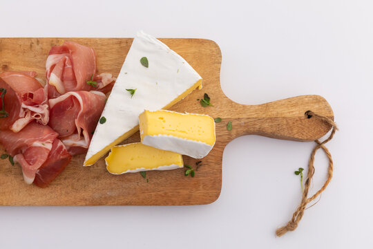 Cheese and ham on wooden board on white background