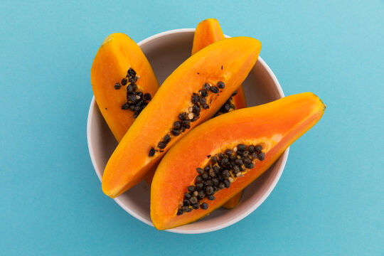 High angle view of bowl of freshly cut papaya on blue background