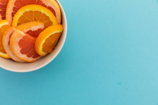 High angle view of bowl of freshly cut orange slices on blue background