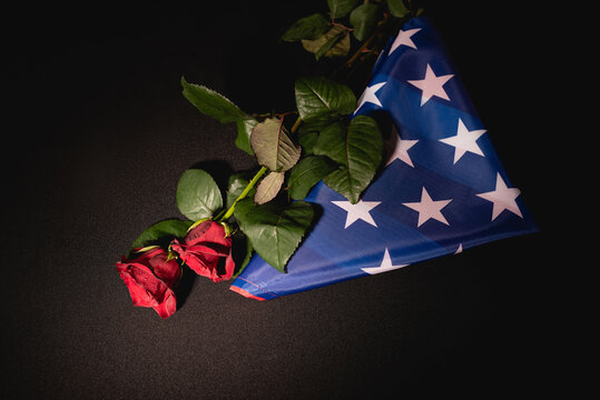 top view of red roses and american flag on black , funeral concept
