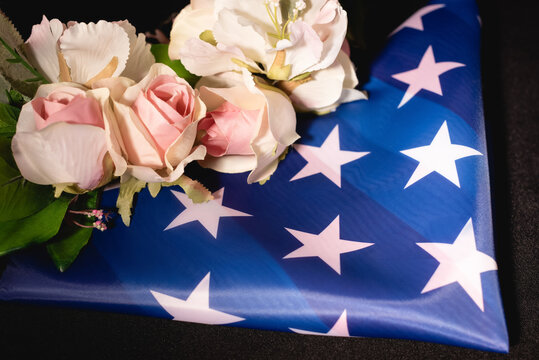 rose bouquet and american flag on black , funeral concept