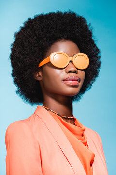african american woman in orange stylish outfit isolated on blue background