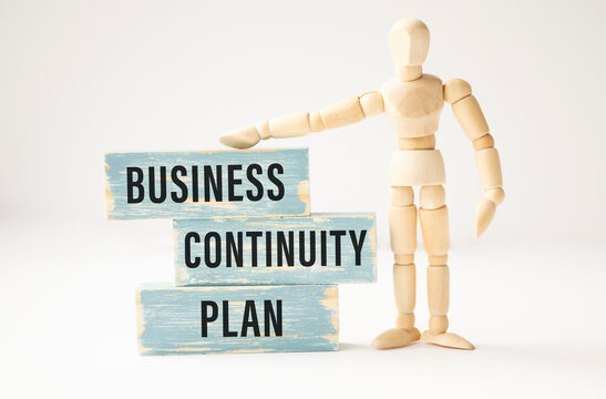 BUSINESS CONTINUITY PLAN, text on wooden block on a white BACKGROUND