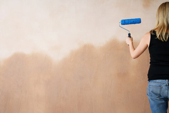 Woman Painting Wall With Paint Roller