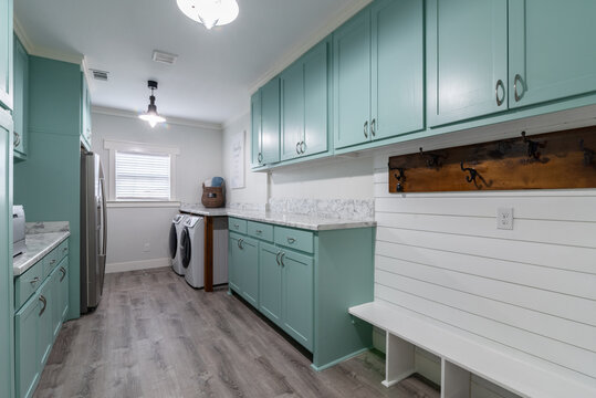 Mint green and white laundry room with mudroom, counter space, oversized,