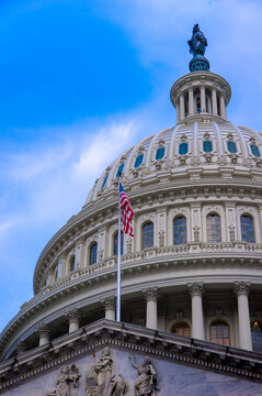 View of American flag on top of entrance to United States Capitol building with marble dome in background with blue sky