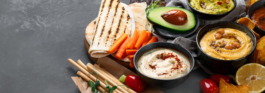 Different kinds of hummus dips with snacks