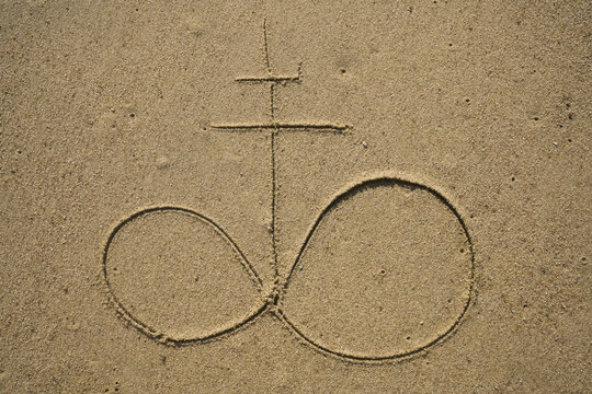 double cross and infinity sign drawing on yellow sand texture. the church of satan and the symbol of leviathan