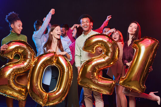 New Years Celebration. Group of young happy multiethnic people holding golden foil balloons in the form of numbers 2021 and having fun at Christmas party