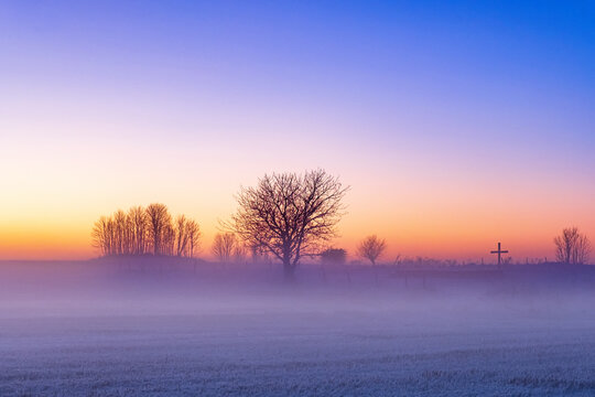 Misty morning in winter with a religious cross and trees in silhouette