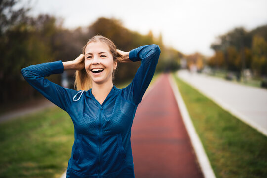 Beautiful adult woman is getting ready for outdoor exercising on cloudy day in autumn.