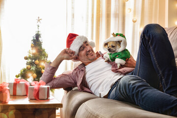 Man resting on sofa with  dog dressed in christmas costume