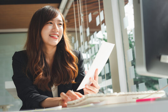 Asian female finance worker holding papers and smiling happily to receive an email informing them of the annual bonus, happy working idea.