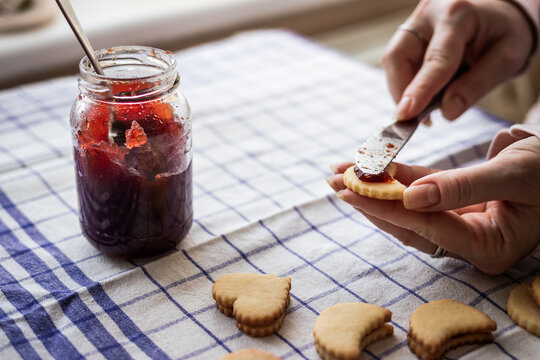 Woman filling traditional Christmas Linzer cookie with red currant jam