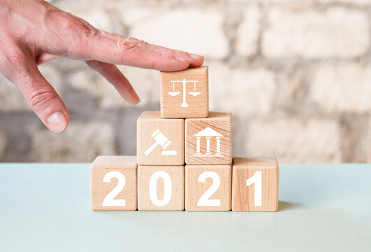 Businessman hand arranging wood block with icon  justice in 2021 new year Labor Law Lawyer Legal Concept.