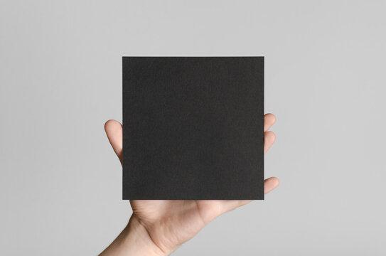 Black Square Flyer / Invitation Mock-Up - Male hands holding a black flyer on a gray background.