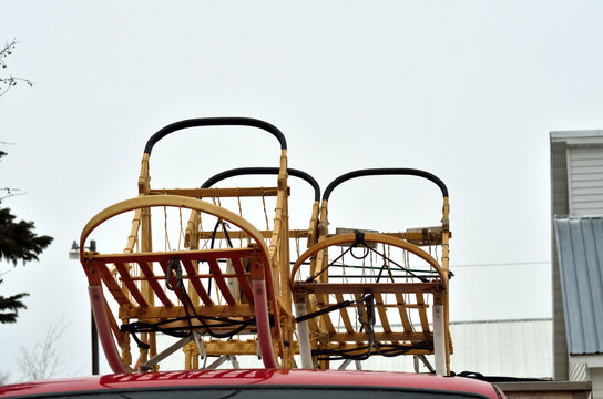 Three sleds use in sled dog travel; often a winter sport for leisure or competitive racing. Sleds are trasported on truck roof.