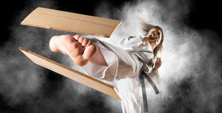 Woman in kimono practicing. Breaking board