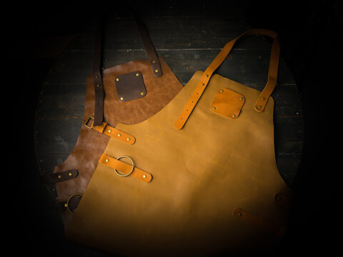 Protective yellow and brown leather apron on dark background