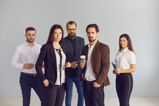 Group portrait of serious young business people standing in studio looking at camera