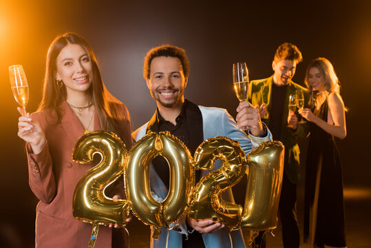 multicultural couple holding glasses of champagne and balloons with 2021 numbers near friends on blurred background on black