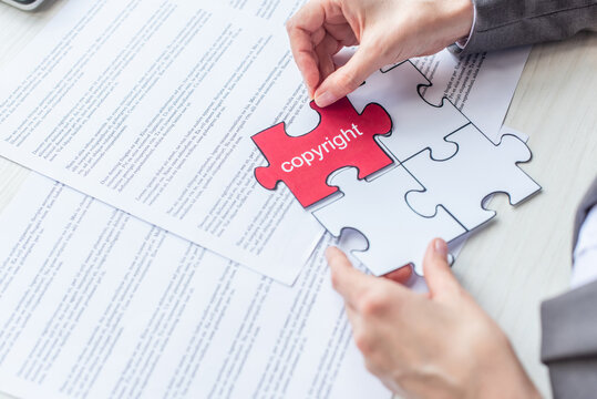 Cropped view of female lawyer putting red jigsaw puzzle with copyright lettering on table with documents, stock image