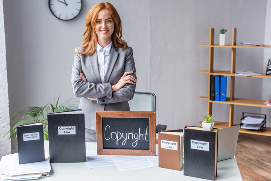lawyer with crossed arms standing near chalkboard with copyright lettering near books on table with pile of documents