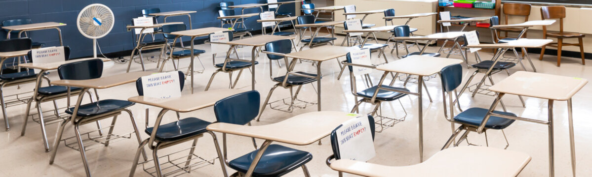 Classroom desks separated six feet apart by row and marked not available