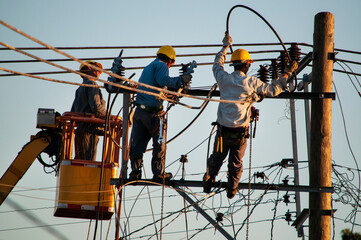 Electric linemen working at heights on the street cables, one on top of the crane and the other on top of a pole secured by belts Wall mural