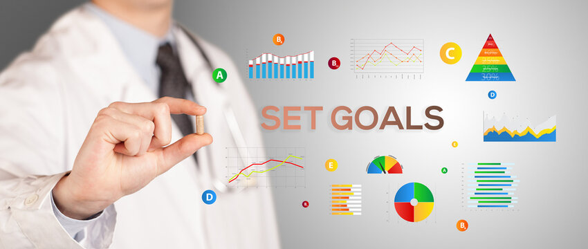 Nutritionist giving you a pill with SET GOALS inscription, healthy lifestyle concept